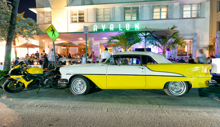 MIAMI BEACH - FEBRUARY 25, 2016: Vintage yellow car parked at night time in Ocean Drive. The city attracts 25 million visitors every year. Éditoriale