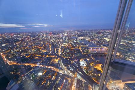LONDON - SEPTEMBER 24, 2016: Aerial view of London Bridges at night. The city attracts 30 million tourists annually. Editorial