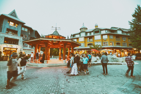 WHISTLER, CANADA - AUGUST 12, 2017: Tourists visit city streets on a summer evening. Whistler is a famous mountain destination.