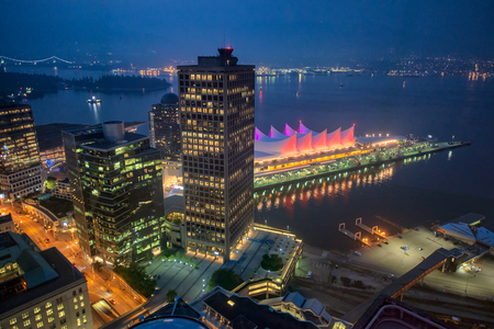 Vancouver skyline with Canada Place at night, aerial view.