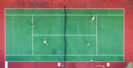 Aerial view of outdoor green and red hard tennis court with four players.