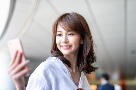 Mooie Japanse vrouw die smartphone binnen metrostation bekijkt.