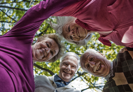 Four elder men and women looking down to camera outdoor. Happiness and retirement concept. Stock fotó