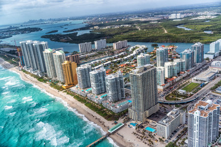 Aerial view of North Miami Beach skyline with sun and clouds.