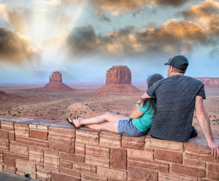 Young couple enjoying sunset view of Monument Valley National Park.