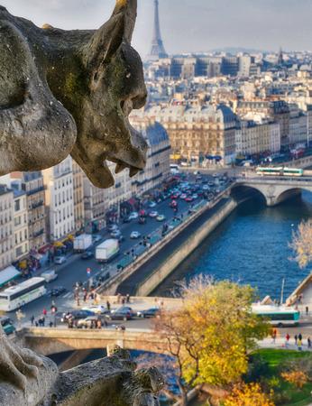 Chimera (Gargoyle) of the Cathedral of Notre Dame de Paris overlooking Paris on a beautiful sunny day.