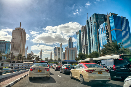 DUBAI, UAE - DECEMBER 10, 2016: City traffic with taxis in Downtown area. Dubai attracts 20 million tourists annually.