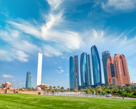 Abu Dhabi modern skyline from Emirates Palace Gardens on a sunny day at sunset.