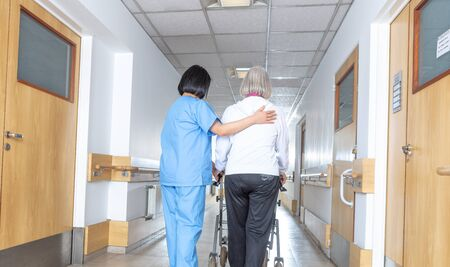 Asian doctor helping elder woman with walker in hospital hallway.