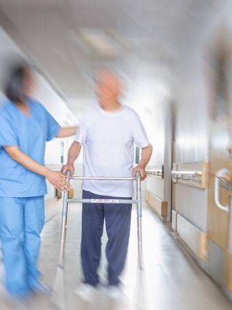 Asian doctor helping elder man with walker in hospital hallway.