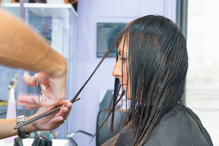 Closeup hairdresser makes hairstyle for woman in 40s in beauty salon.