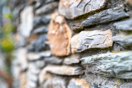 Street wall with protruding rocks, blurred background
