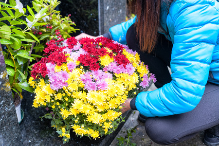 Close-up of a Sad Woman Holding Fowers in front of a Loved ones Gravestone. Focus on the Bouquet.