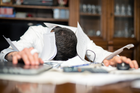 Desperate man submerged from work in his office. Papers and laptop with head on the desktop.