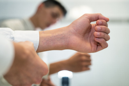 Young man tying the cuffes in front of mirror. Detail on hands Stock Photo
