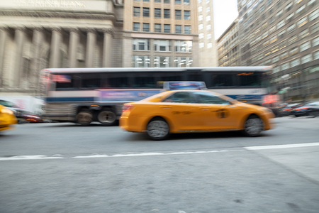 Blurred view of fast moving taxis and bus in Manhattan.