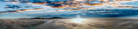 Panoramic aerial view of countryside scenario surrounded by fog, view from drone above the clouds at sunset.