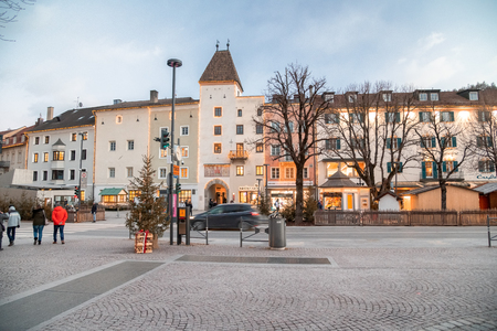 BRUNICO, ITALY - JANUARY 3rd, 2019: Main city square with tourists on a winter sunset. The city is a famous italian mountain destination. Editorial