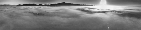 Panoramic aerial view of countryside scenario surrounded by fog, view from drone above the clouds. Imagens - 118513009