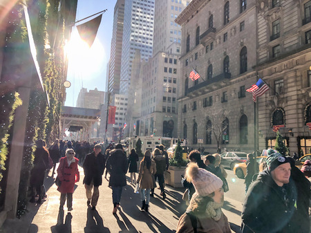 NEW YORK CITY - DECEMBER 7, 2018: People walk along fifth avenue, backlit scene. The city attracts 50 million tourists annually.