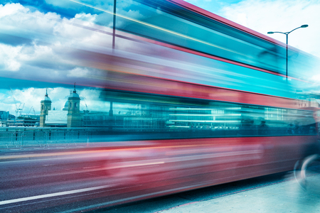 London Red Bus speeding up in London. Blurred view with city skyline on background.
