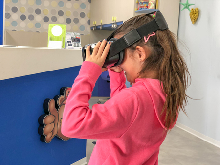 Little caucasian cute girl wearing virtual reality goggles analyzing bedroom with VR visor.
