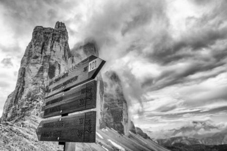 Three Peaks of Lavaredo with road signs in summer season, Italian Alps.
