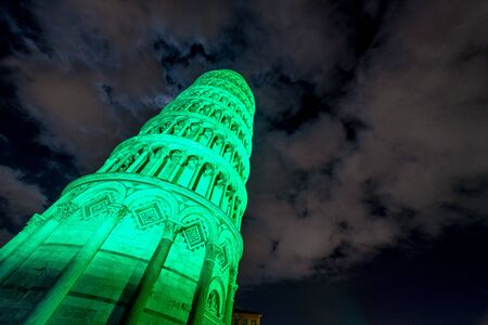 Pisa Tower in Miracles Square for St Patricks Day illuminated by green lights, Tuscany - Italy.