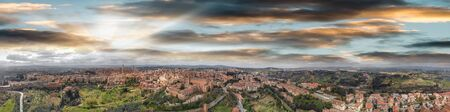 Amazing panoramic aerial view of Siena medieval skyline at sunset, Tuscany .