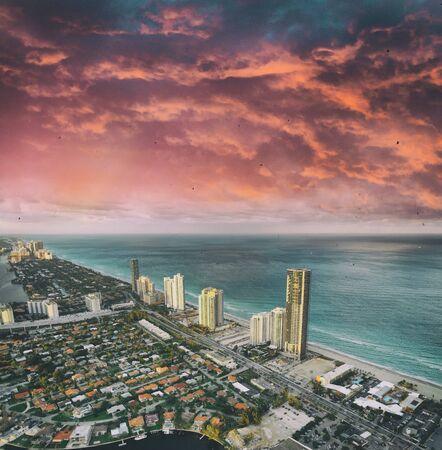 Incredibile skyline di Miami Beach. Vista aerea degli edifici della città dall'elicottero su un tramonto nuvoloso.