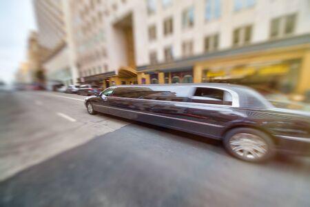 Long Limousine speeding up along city street.
