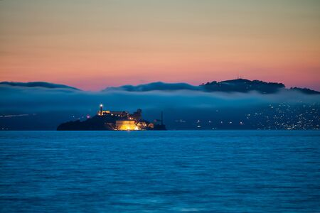 Alcatraz Island at sunset surrounded by fog and mountains.