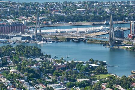 SYDNEY - OCTOBER 2015: Aerial view of Anzac Bridge on a beautiful sunny day. The city attracts 20 million people annually. Imagens