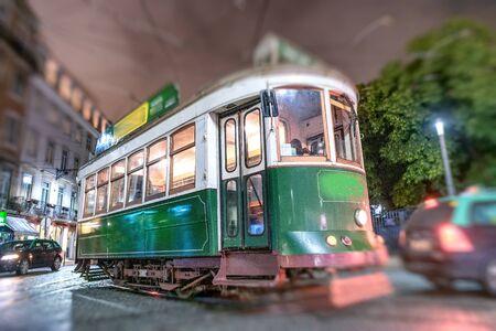Green tram in Lisbon at night.