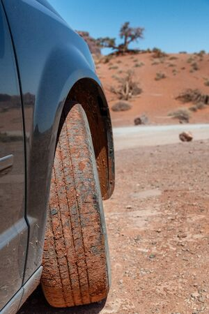 Red sand under car tyre ona clear sunny day.