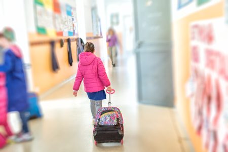 Young caucasian girl at school going into her classroom handing trolley.