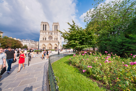 PARIS - JUNE 2014: Notre Dame Cathedral with tourists along the square garden. Notre Dame is visited by 12 million people every year.