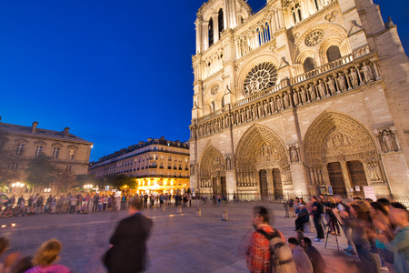 PARIS - JUNE 2014: Notre Dame Cathedral at night with tourists. Notre Dame is the most visited monument in Europe.