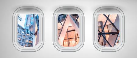 Bâtiments modernes de Londres vus à travers trois hublots d'avion. Concept de vacances et de voyage.