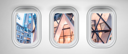 London modern buildings as seen through three aircraft windows. Holiday and travel concept.