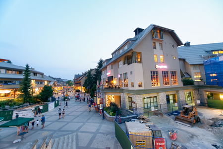 WHISTLER, CANADA - AUGUST 12, 2017: Tourists enjoy city center on a summer night. Whistler is a famous mountain destination in British Columbia.