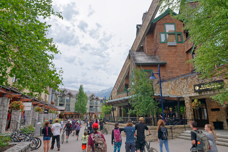 WHISTLER, CANADA - AUGUST 12, 2017: Tourists enjoy city center on a summer day. Whistler is a famous mountain destination in British Columbia. Editorial