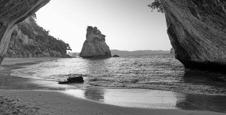 Cathedral Cove framed by arch on the beach, Coromandel, New Zealand.