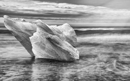 Jokulsarlon Diamond Beach with iceberg on a sunny day, Iceland. Long exposure view.