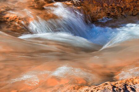 Blurred view of flowing waters against red rocks. 版權商用圖片