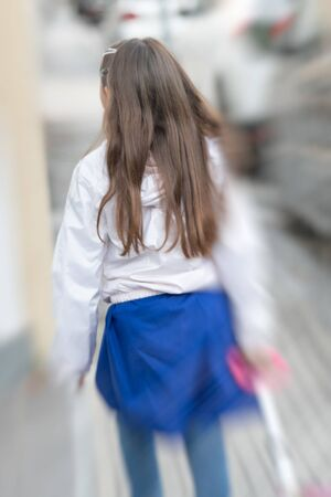 Back view of young schoolgirl arriving at school with the backpack. Happiness and education concept.