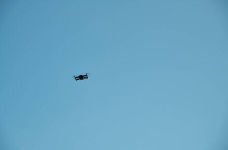 Black drone in the blue sky. Freedom concept.
