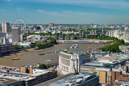 Aerial view of London with buildings along river Thames in summer.