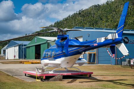 AIRLIE BEACH, AUSTRALIA - AUGUST 25, 2018: Helicopter in Whitsunday Airport ready for islands excursion. The city is the gateway to the Whitsunday Islands.