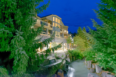 WHISTLER, CANADA - AUGUST 12, 2017: Tourists visit city center on a summer night. Whistler is a famous mountain destination in British Columbia.